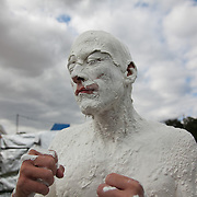 A man is covered in thick white paint which only shows his knuckles,mouth and nostrils. He is a one man performance and part of the Super Normal art festival held in Oxfordshire on the land of the Braziers Park. The festival is a mix of live music and performance art.