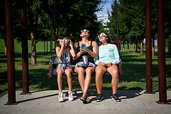 August 21, 2017 - Louisville, Kentucky, U.S. - A family sits on a swing and uses solar filtered glassed to look at the sun during a solar eclipse in Louisville, Kentucky, Monday, August 21, 2017. (Credit Image: © Bryan Woolston via ZUMA Wire)