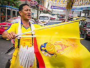 04 DECEMBER 2012 - BANGKOK, THAILAND: A vendor wearing yellow sells Thai flags and the flag of the Thai Monarchy in front of Siriraj Hospital. Yellow is the official color of the Thai King, who celebrates his 85th birthday Wednesday, Dec. 5. The King lives in Siriraj. He is expected to make a rare public appearance and address the nation from Mukkhadej balcony of the Ananta Samakhom Throne Hall in the Royal Plaza. The last time he did so was in 2006. His birthday is a public holiday in Thailand and hundreds of thousands of people are expected to jam the streets around the Royal Plaza and Grand Palace to participate in the festivities.    PHOTO BY JACK KURTZ