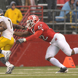 Dec 5, 2009; Piscataway, NJ, USA; West Virginia running back Noel Devine (7) eludes Rutgers linebacker Steve Beauharnais (42) during second half NCAA Big East college football action in West Virginia's 24-21 victory over Rutgers at Rutgers Stadium.