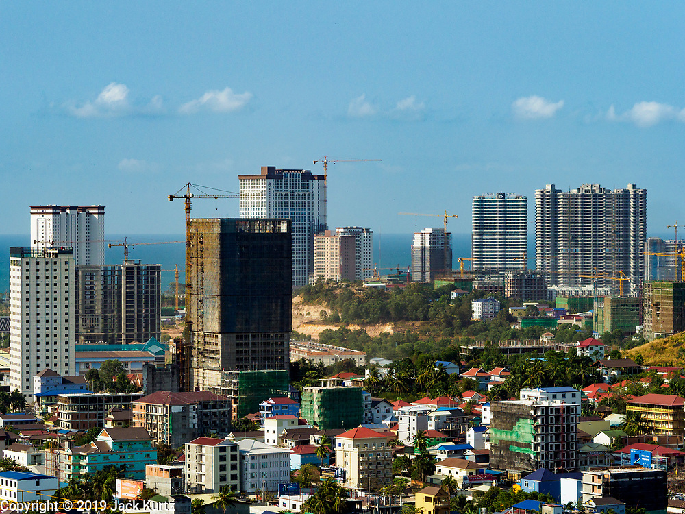 """15 FEBRUARY 2019 - SIHANOUKVILLE, CAMBODIA:  Construction sites for Chinese resorts and casinos rise over downtown Sihanoukville. There are about 80 Chinese casinos and resort hotels open in Sihanoukville and dozens more under construction. The casinos are changing the city, once a sleepy port on Southeast Asia's """"backpacker trail"""" into a booming city. The change is coming with a cost though. Many Cambodian residents of Sihanoukville  have lost their homes to make way for the casinos and the jobs are going to Chinese workers, brought in to build casinos and work in the casinos.    PHOTO BY JACK KURTZ"""