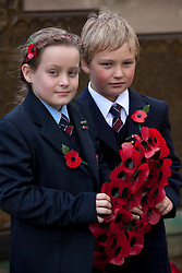 © under licence to London News Pictures 11/11/2010 Solihull School, West Midlands, came to a standstill at 11am this morning to take part in the school Armistice service. Pupils Ellie Berrow (9) and Jack Rootkin-Gray (8) hold the pupils wreath laid during the service...
