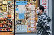 3rd March, 2021. Cheltenham, England. A man walks past a vape shop in the town centre wearing a mask.