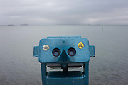A 50p a go binoculars looking out to the Thames estuary waters, on 17th September 2016, on the Western Esplanade, at Southend, Essex, England. Looking out towards a grey sky on the Thames river estuary as it widens before flowing into the English Channel. Southend-on-Sea is a seaside town on the north side of the Thames estuary 40 miles 64 km east of central London. In its heyday, the working class visited from the capital when train transport allowed them to enjoy its beaches and the worlds longest pier. Its splendour faded on the advent of package holidays to Spain etc.