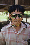 PENAN SUNGLASSES, MALAYSIA. Sarawak, Borneo, South East Asia. Penan wearing  sunglasses. Tropical rainforest and one of the world's richest, oldest eco-systems, flora and fauna, under threat from development, logging and deforestation. Home to indigenous Dayak native tribal peoples, farming by slash and burn cultivation, fishing and hunting wild boar. Home to the Penan, traditional nomadic hunter-gatherers, of whom only one thousand survive, eating roots, and hunting wild animals with blowpipes. Animists, Christians, they still practice traditional medicine from herbs and plants. Native people have mounted protests and blockades against logging concessions, many have been arrested and imprisoned.