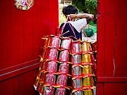 """26 FEBRUARY 2019 - BANGKOK, THAILAND: A man carries """"ghost gold"""" into a Wat Mangon Kamalawat in Bangkok's Chinatown. Ghost gold is burned as an offering for ancestors. Bangkok has one of the largest """"Chinatown"""" districts in the world. About 14% of all Thais have some Chinese ancestry and Chinese cultural practices are incorporated in many facets of Thai daily life.       PHOTO BY JACK KURTZ"""