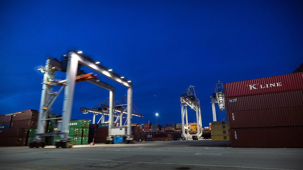 HOLD FOR JENNY KANE** In this July, 5, 2018 photo, a rubber tire gantry moves to the next stack of shipping containers while massive post-Panamax cranes work a ship, Thursday, July 5, 2018, at the Port of Savannah in Savannah, Ga. The U.S. hiked tariffs on Chinese imports Friday and Beijing said it immediately retaliated in a dispute between the world's two biggest economies. (AP Photo/Stephen B. Morton)