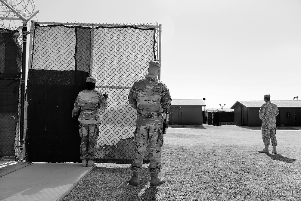 """Military guards at the prison camp at Guantanamo, Cuba, Jan 28 2017. The guards turn away their faces so you cannot identify them. It is standard operation procedure when pictures are made. When you work as a journalist at the Guantanamo you work under military censorship and all your material is checked every day and approved for publication.<br /> The prison camp on the Guantánamo naval base was the creation of President George W. Bush. The prison camp was considered an important part of the US war on terrorism. Over the years, 779 people have been brought to the camp. 41 people are still detained. Of them, 26 people count as """"forever prisoners"""", indefinite detainees under the Law of War. Two prisoners have been in the camp since it was opened in January 2002. The last prisoner taken to the camp came in March 2008. The so-called war on Terror and the Guantanamo prison camp have been heavily criticized for violation of human rights regarding torture and habeas corpus.<br /> It is unclear what US President Donald Trump wants to do with the camp, but during the election campaign he said that he would fill Guantánamo Bay with """"bad dudes"""". Photo by Ola Torkelsson<br /> Copyright Ola Torkelsson ©"""