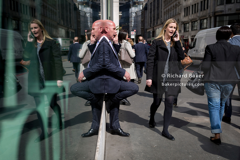 A symmetrical lady and a gentleman wearing a pinstripe suit talks on his phone, reflected in plate glass in the City of London, the capital's financial district also known as the Square Mile, on 6th April 2017, in London, England.
