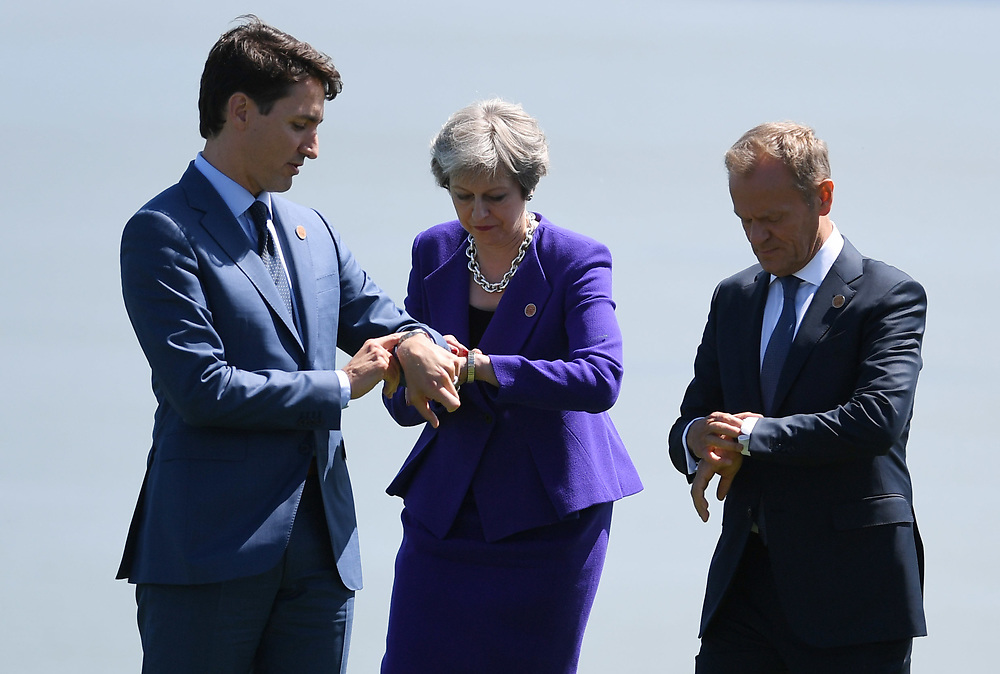 Canada's Prime Minster Justin Trudeau (L) President of the European Council Donal Tusk (R) and Britain's Prime Minster Theresa May (C) check the time after posing for the Family Portrait at the G7 summit in Charlevoix in Canada 08 June 2018. The G7 Summit runs from 8 to 9 June in Charlevoix, Canada.