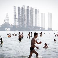 Baku, Azerbaijan, 24 July 2012<br /> Azeri people swim beside an oil exploitation platform close to Baku.<br /> Photo: Ezequiel Scagnetti