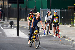 © London News Pictures. 25/08/2016. A cyclist ignores the new cycle lane (right) and chose to join moving traffic while using a cycle lane on Abingdon Street, approaching Parliament Square. Cyclists repeatedly ignore new cycle lanes installed around westminster in central London. Between the hours of 8am and 9am on Wednesday 24/08/2016, 266 (two hundred and sixty six) cyclists passed through the red light at one of the newly installed  bike lanes and only 15 (fifteen) cyclists stopped.  The light system is designed to allow either vehicles or cyclists to pass at one time in order to make the junction safer for cyclists..... **VIDEO AVAILABLE** Photo credit: London News Pictures.