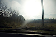 rural country side road seen through the window of a car