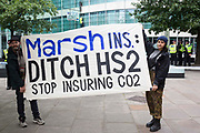 Climate activists from HS2 Rebellion hold a banner in front of two fellow activists who scaled the Marsh insurers building in the City of London in protest against the HS2 high-speed rail project on 2nd September 2021 in London, United Kingdom. Marsh JLT Specialty are the main insurers for HS2.