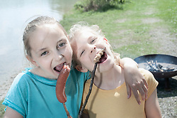 Two friends eating sausage and bread at lakeshore, Bavaria, Germany