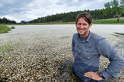 Sean Fitzgerald in pond covered in white wildflowers, Vermejo Park Ranch, New Mexico, USA.