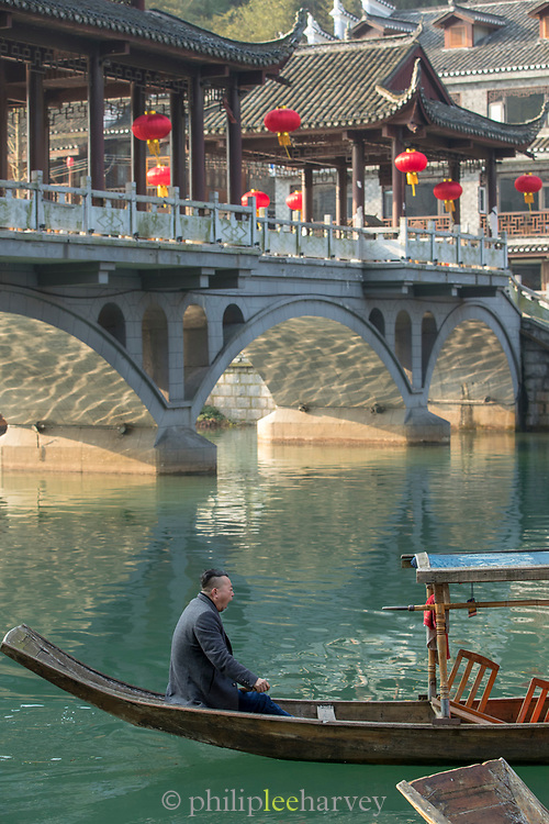 Side view of a mature man sitting in a boat in a river and a traditional Chinese style bridge in the background, Fenghuang, Hunan Province, China