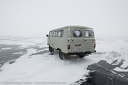 Russian vans on an excursion driving 30-miles across Lake Baikal on the meter-thick ice after the Baikal Mile Ice Speed Festival. Maksimiha, Siberia, Russia. Sunday, March 1, 2020. Photography ©2020 Michael Lichter.