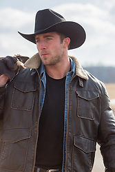 All American Cowboy in a leather jacket and sheepskin collar carrying a saddle on a ranch
