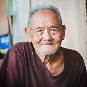 Portrait of elderly Thai man in Khlong Toei neighbourhood of Bangkok