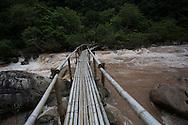 A man crosses a river on a bamboo foot bridge in Suoi Nuoc Mooc, Phong Nha -Ke Bang National Park, Quang Binh Province, Vietnam, Southeast Asia