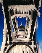 Morning light illuminating ice-covered catwalk and South Haven Pier Lighthouse, Black River, Lake Michigan, South Haven, Michigan.
