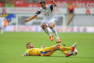 Neil Taylor of Swansea City jumps over the Petrolul Ploiesti defender.<br /> UEFA Europa league, play off round, 1st leg match, Swansea city v FC Petrolul Ploiesti at the Liberty stadium in Swansea on Thursday 22nd August 2013. pic by Phil Rees , Andrew Orchard sports photography,