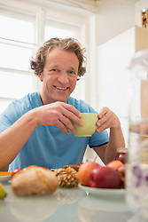 Smiling man sitting at breakfast table in kitchen
