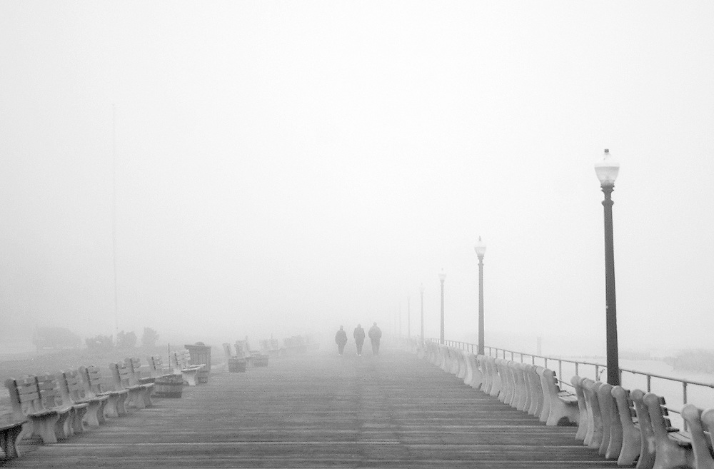 Pedestrians walk down the boardwalk of Ocean Grove, New Jersey during a foggy and humid afternoon on April 3, 2009.