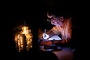 Using candles, Claudio Corallo is writing notes while sitting inside his house on the island of Principe, Sao Tome and Principe, (STP) a former Portuguese colony in the Gulf of Guinea, West Africa.