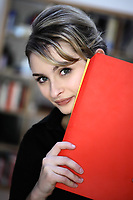 portrait of a cute and smiling businesswoman at the office desk hiding behind files