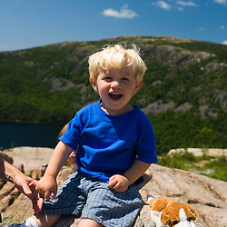 A young boy (age 2) and his stuffed puppy friend on the summit of South Bubble Mountain in Maine's Acadia National Park.