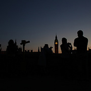 Tourists photograph sunset behind Big Ben and the Houses of parliament. Big Ben is to chime non-stop for three minutes to help ring in the London 2012 Olympics. Special permission had to be gained for the hour bell at the Palace of Westminster to toll out of its regular sequence. It will strike more than 42 times between 8.12am and 8.15am on 27 July to herald the beginning of the first day of Games. It will be the first time Big Ben has been rung outside its regular schedule since 15 February 1952, when it tolled every minute for 56 strokes for the funeral of King George VI. London 2012 Olympic games  London, UK. 22nd July 2012. Photo Tim Clayton