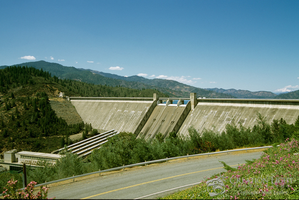 Shasta Dam is a concrete gravity arch dam across the Sacramento River in California. Completed between 1938 and 1945. The dam is 602 ft (183 m) high and 3,460 ft (1,050 m) long, with a base width or thickness of 543 ft (166 m). The reservoir created by Shasta Dam is known as Shasta Lake.