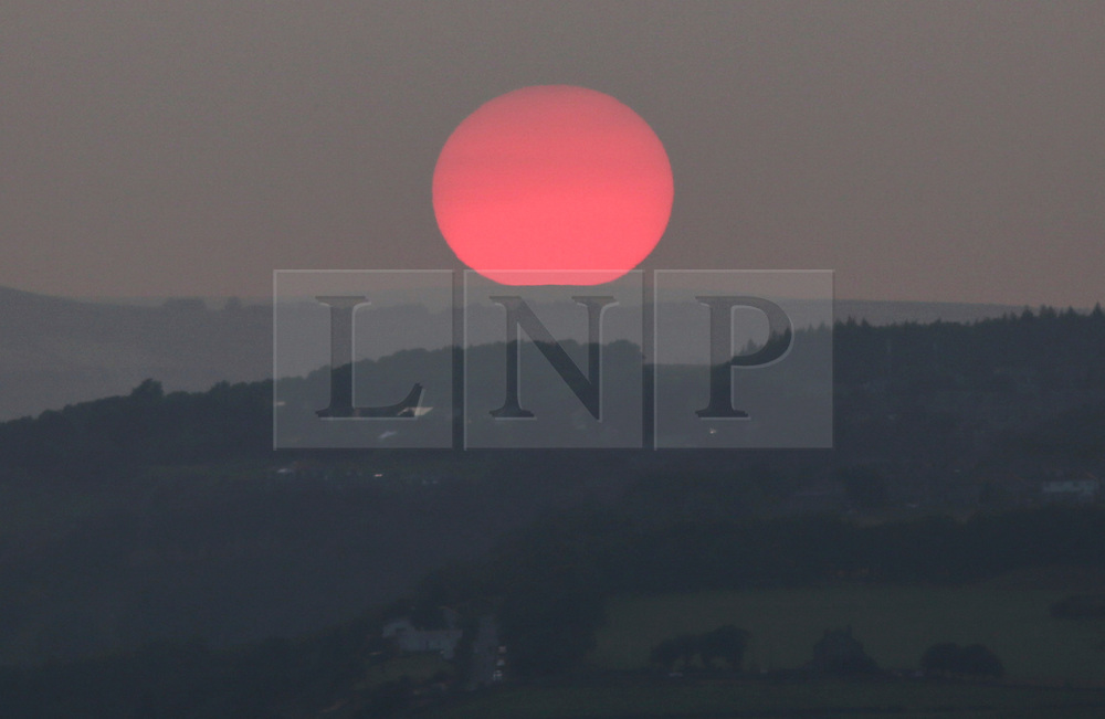 © Licensed to London News Pictures. 21/07/2021. Huddersfield, UK. The Sun sets behind the hills of West Yorkshire on Wednesday evening after another day of high temperatures. Photo credit: Adam Vaughan/LNP