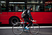 Japanese cyclist stops amidst traffic and a london bus. Cycling is increasingly popular in London as people try to avoid public transport.