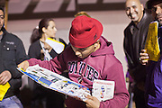 "24 NOVEMBER 2011 - PHOENIX, AZ:  Abdul Manan (CQ) from Glendale, reads the Best Buy circular while he waits for the Best Buy store on Thunderbird and I 17 in Phoenix to open. ""Black Friday,"" the unofficial start of the holiday shopping season started even earlier than normal. Many stores, including Target and Best Buy, opened at midnight. The Best Buy at Thunderbird and I 17 showed a Harry Potter movie on the side of a rented truck in the parking lot to keep people amused while they waited for the store to open.   Photo by Jack Kurtz"