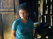 Wearing her traditional headdress and a modern t-shirt, a married Mouchi ethnic minority woman stands outside her wooden home in Ban Terka, Phongsaly province, Lao PDR. One of the most ethnically diverse countries in Southeast Asia, Laos has 49 officially recognised ethnic groups although there are many more self-identified and sub groups. These groups are distinguished by their own customs, beliefs and rituals. Details down to the embroidery on a shirt, the colour of the trim and the type of skirt all help signify the wearer's ethnic and clan affiliations.