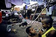 Childen play amidst the squalor of their slum which lies under Rio de janeiro city overpass, Brazil