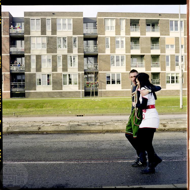 Twee carnavalsvierders lopen na afloop van de optocht over straat. In Zevenaar, dat gelegen is in De Liemers, wordt volop carnaval gevierd, onder andere met een optocht. De plaats wordt tijdens carnaval omgedoopt tot Boemelburcht. <br /> <br /> The carnival parade in Zevenaar. Zevenaar is located in De Liemers, a district in the eastern part of the Netherlands. During carnival Zevenaar is called Boemelburcht.