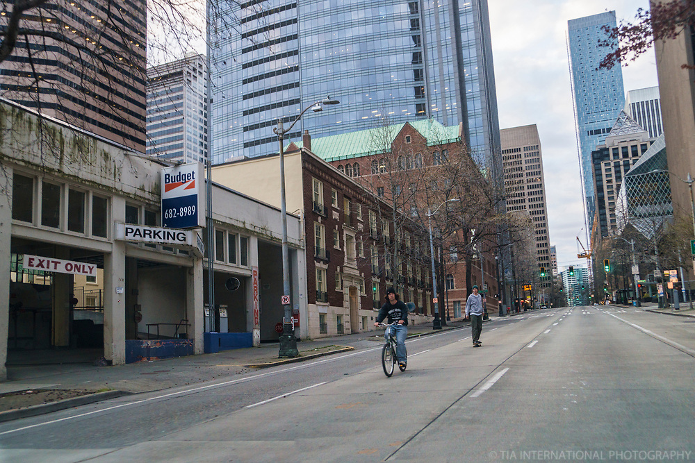 Because this main thoroughfare in the downtown neighborhood is so empty, this cyclist and skateboarder exhibit no fear of traveling in the *opposite* direction of the typical flow of traffic by cars and trucks. Notice the green traffic lights behind them. (April 5, 2020)
