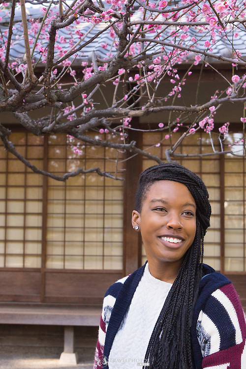 A young lady travelling in Japan enjoying plum flowers at early bloom at Nagoya Castle.
