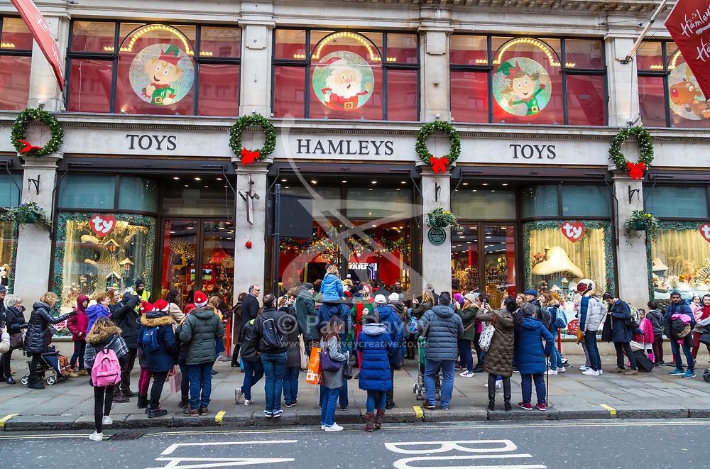 London, December 24 2017. Crowds grow in London's west end on Christmas eve as last minute shoppers hunt for gifts. PICTURED: Hundreds of shoppers queue awaiting the midday opening of Hamleys Toy Store in Regent Street. © SWNS