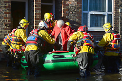 © Licensed to London News Pictures. 27/12/2015. York, UK.  A mountain rescue team evacuate an elderly resident from a flooded property in York City centre. Large areas of the North of England have been hit by severe flooding following unusually heavy rainfall in December. Photo credit: Ben Cawthra/LNP