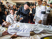 12 OCTOBER 2104 - BANG BUA THONG, NONTHABURI, THAILAND: Scented oils are poured over the body of Apiwan Wiriyachai during the first day of funeral rites for Apiwan at Wat Bang Phai in Bang Bua Thong, a Bangkok suburb, Sunday. Apiwan was a prominent Red Shirt leader, member of the Pheu Thai Party of former Prime Minister Yingluck Shinawatra, and a member of the Thai parliament. The military government that deposed the elected government in May, 2014, charged Apiwan with Lese Majeste for allegedly insulting the Thai Monarchy. Rather than face the charges, Apiwan fled Thailand to the Philippines. He died of a lung infection in the Philippines on Oct. 6. The military government gave his family permission to bring him back to Thailand for the funeral. He will be cremated later in October. The first day of the funeral rites Sunday drew tens of thousands of Red Shirts and their supporters, in the first Red Shirt gathering since the coup.    PHOTO BY JACK KURTZ