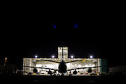 """In the darkness of a taxiway at the southern end of Heathrow Airport, the bright lights of an engineering hangar spill out into the night. A Boeing 747 Jumbo jet sits nose-in behind another during a scheduled set of maintenance tasks that every aircraft needs to keep to in order for its continued airworthiness. The unmistakable shape of this large aircraft is a half-silhouette against the intensity of the hangar and blue flare spots that arise from the internal glass in the camera's lens. From writer Alain de Botton's book project """"A Week at the Airport: A Heathrow Diary"""" (2009). ."""