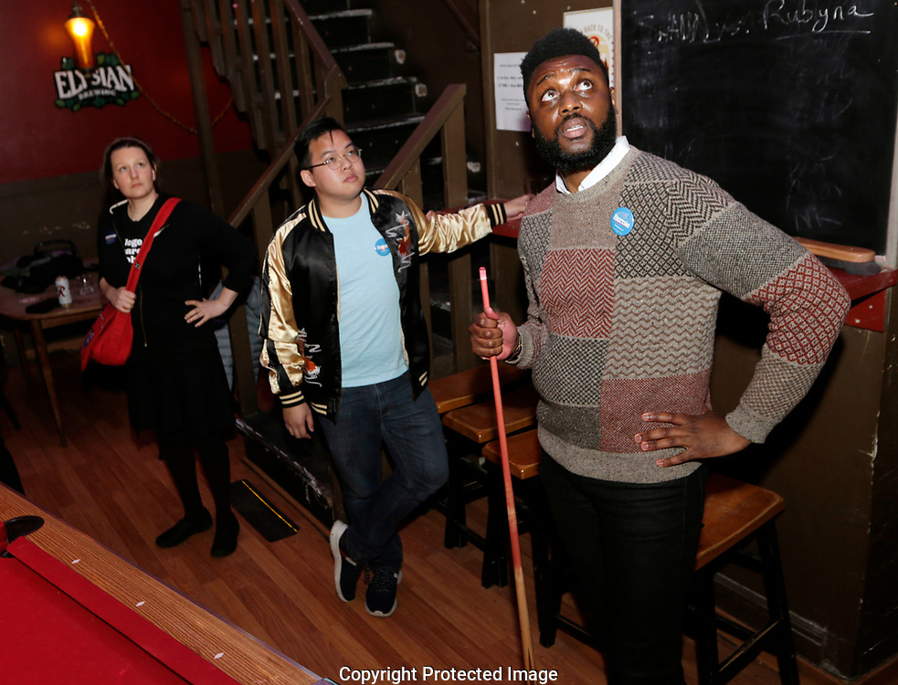 Shaun Scott, right, Rico Doan, center, and Amy Madden, left, watch the early returns at an informal campaign party for Democratic presidential candidate Sen. Bernie Sanders, I-Vt. as the first results come in for the Washington State primary, Tuesday, March 10, 2020, in Seattle. (AP Photo/John Froschauer)