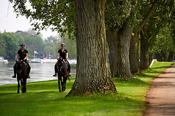 © London News Pictures. 12/05/2016. Windsor, UK. Two women on horseback make their way along the banks of the River Thames during the first day of the 2016 Royal Windsor Horse Show, held in the grounds of Windsor Castle in Berkshire, England. The opening day of the event was cancelled due to heavy rain and waterlogged grounds. This years event is part of HRH Queen Elizabeth II's 90th birthday celebrations.  Photo credit: Ben Cawthra/LNP