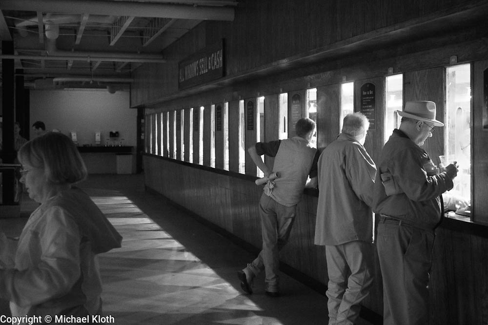 Three men at the betting window at Keeneland Race Course, Lexington, KY.  Infrared (IR) photograph by fine art photographer Michael Kloth. Black and white infrared photographs