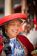 Local Quechua woman in traditional dress laughing at Chinchero Town Sunday Market, Cusco Region, Peru, South America